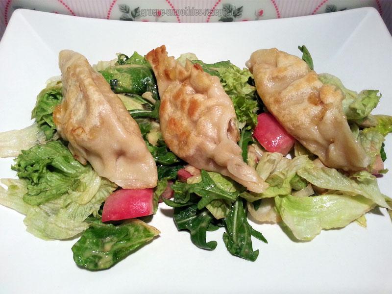 Kartoffel-Piroggen (Pierogi) mit Sauerkraut auf einem Rucola-Radieschen-Eisberg-Salat-Mix mit Tahini-Dressing