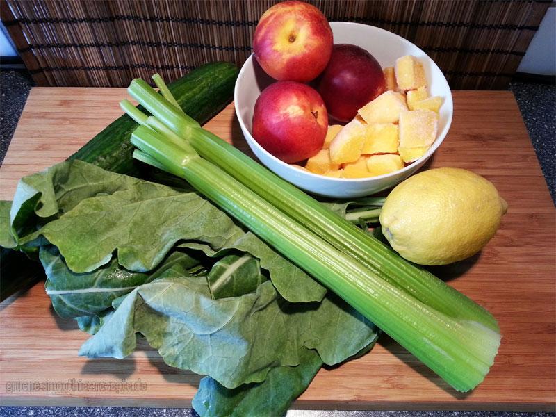Die Zutaten für den grünen Smoothie mit Kohlrabiblätter, Nektarinen, Mango, Gurke, Staudensellerie und Zitrone