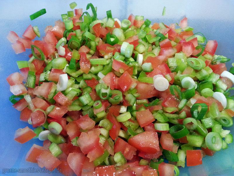 Die Frühlingszwiebeln und die Tomaten für den Bulgursalat (Kisir) klein schneiden
